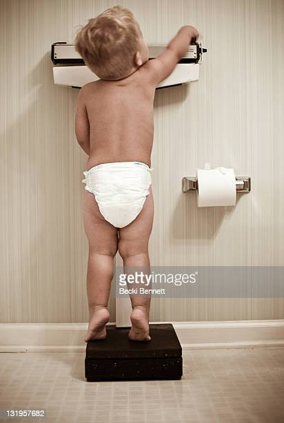 young baby boy weighing himself on bathroom scales - diaper boy stock photos and pictures