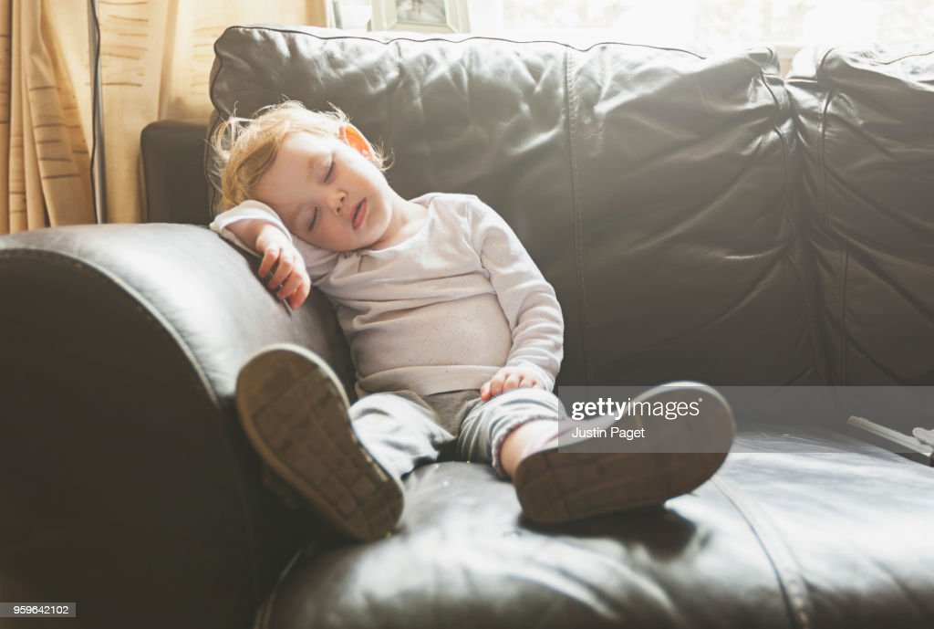 Young baby girl falls asleep on sofa : Stock-Foto
