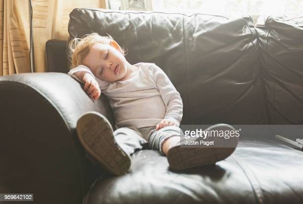 young baby girl falls asleep on sofa - tired stock pictures, royalty-free photos & images