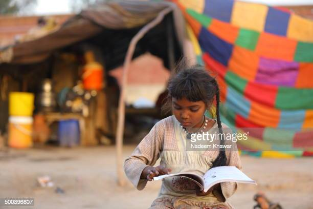 CONTENT] A young baby girl studying in front of her slum Education the basic right of human butt very hard to achieve for the people who lives in...