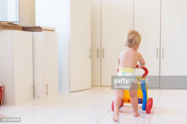 Young baby practicing how to walk with his walker in a living room.