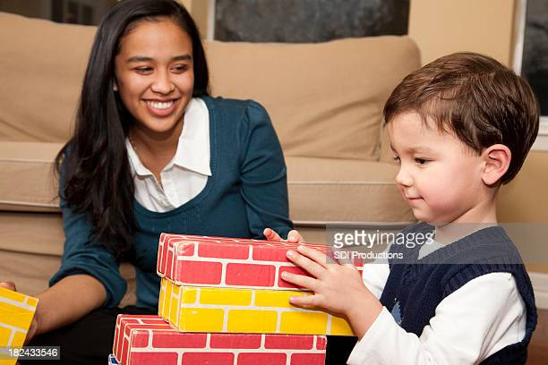 Young Baby Sitter Playing Blocks with Toddler Boy