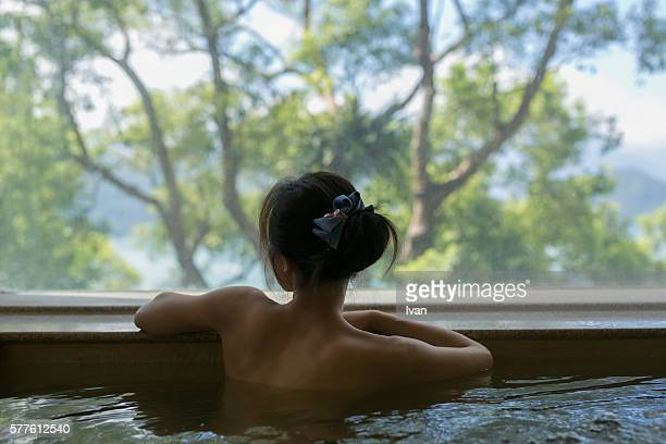 A Young BackLess Woman Bathing at Hot Spring Resort with Beautiful Landscape View