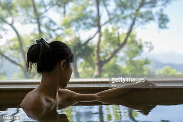 a young backless woman bathing at hot spring resort with beautiful landscape view - hot spring stock pictures, royalty-free photos & images