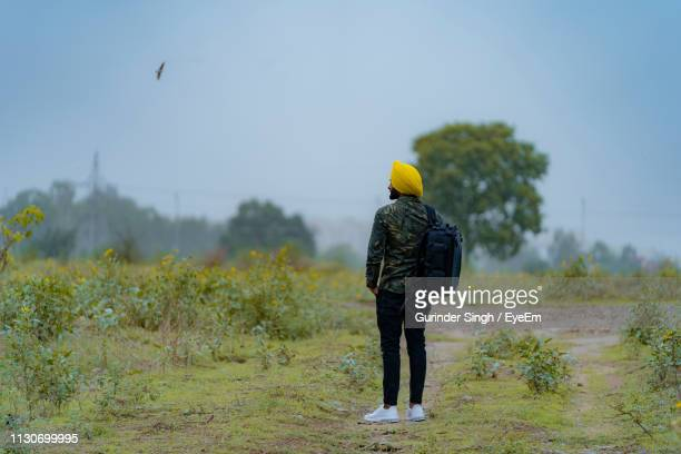 Young Backpack Man Standing On Field