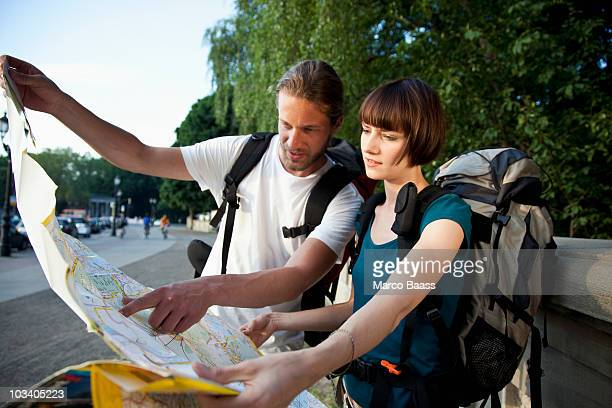 A young backpacker couple looking at a city map