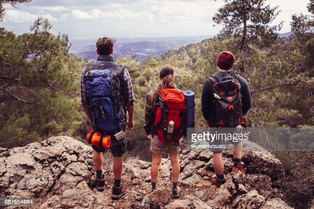 Young backpacker friends enjoying the view from the mountain peak