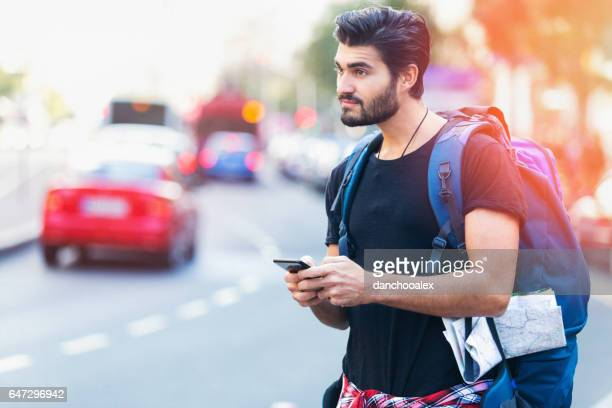 Young backpacker in the city using smart phone
