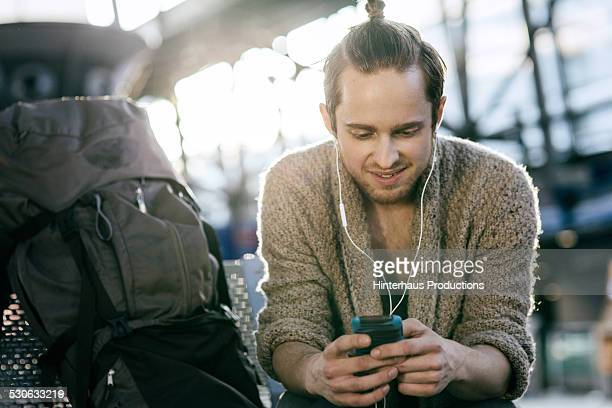 Young Backpacker With Smart Phone At Airport