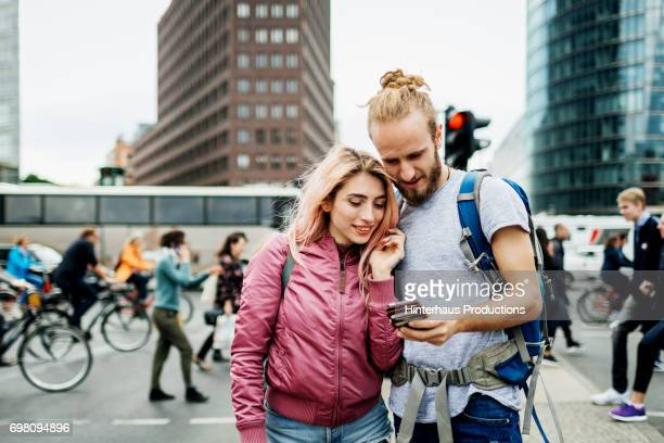 young backpackers checking smartphone together in busy city street - rucksacktourist stock-fotos und bilder