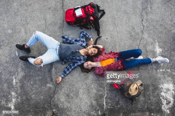 young backpackers lying on the ground - generic location stock pictures, royalty-free photos & images