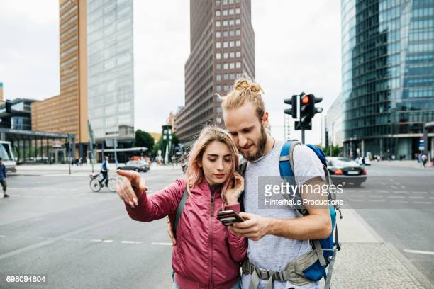 a young backpacking couple standing on corner of busy city street - tourist stock-fotos und bilder