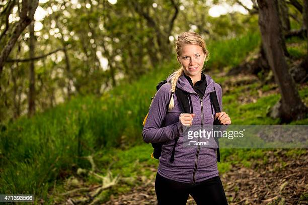 Young Backpacking Woman Hiking on a Green Forest Trail