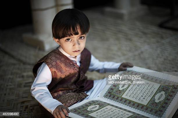 A young Bahraini Shiite Muslim boy poses for a picture as he reads the Koran Islam's holy book during the holy fasting month of Ramadan at a mosque...