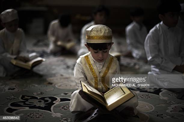 A young Bahraini Shiite Muslim boy reads the Koran Islam's holy book during the holy fasting month of Ramadan at a mosque in the village of Sanabis...