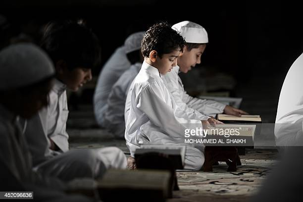 Young Bahraini Shiite Muslim boys read the Koran Islam's holy book during the holy fasting month of Ramadan at a mosque in the village of Sanabis...