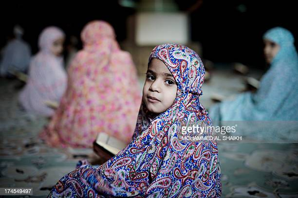 A young Bahraini Shiite Muslim girl poses for a picture as she reads the Koran Islam's holy book during the holy fasting month of Ramadan at a mosque...