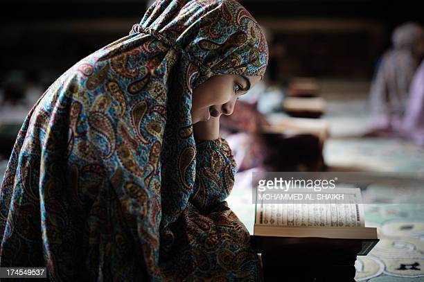 A young Bahraini Shiite Muslim girl reads the Koran Islam's holy book during the holy fasting month of Ramadan at a mosque in the village of Sanabis...