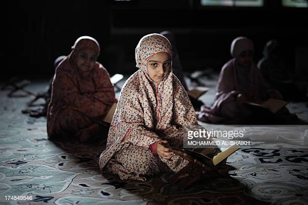Young Bahraini Shiite Muslim girls read the Koran Islam's holy book during the holy fasting month of Ramadan at a mosque in the village of Sanabis...