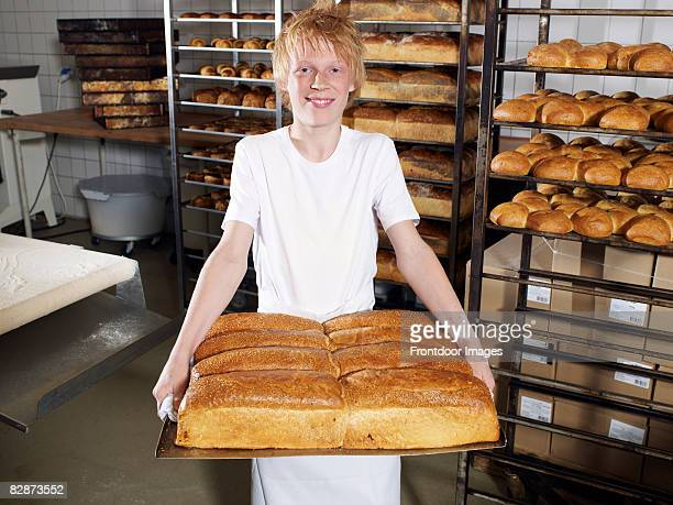 Young baker (14) carrying tray of fresh bread