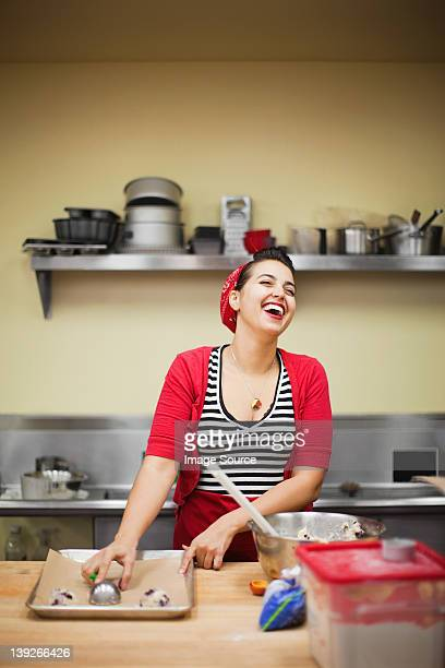 Young baker laughing while preparing food