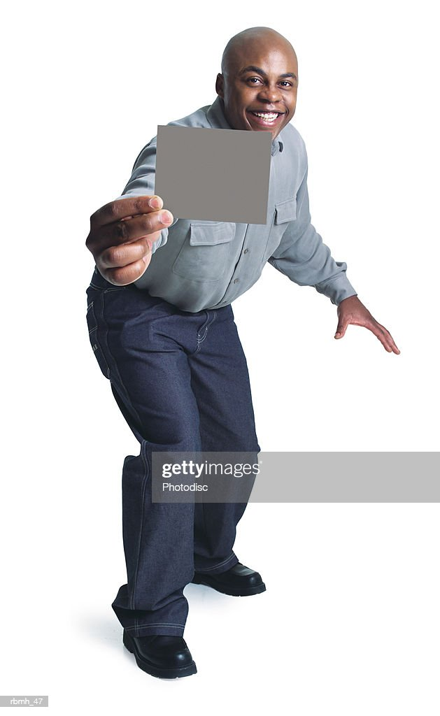 young bald african american man wears dark pants grey shirt steps forward holding blank sign smiles : Stockfoto