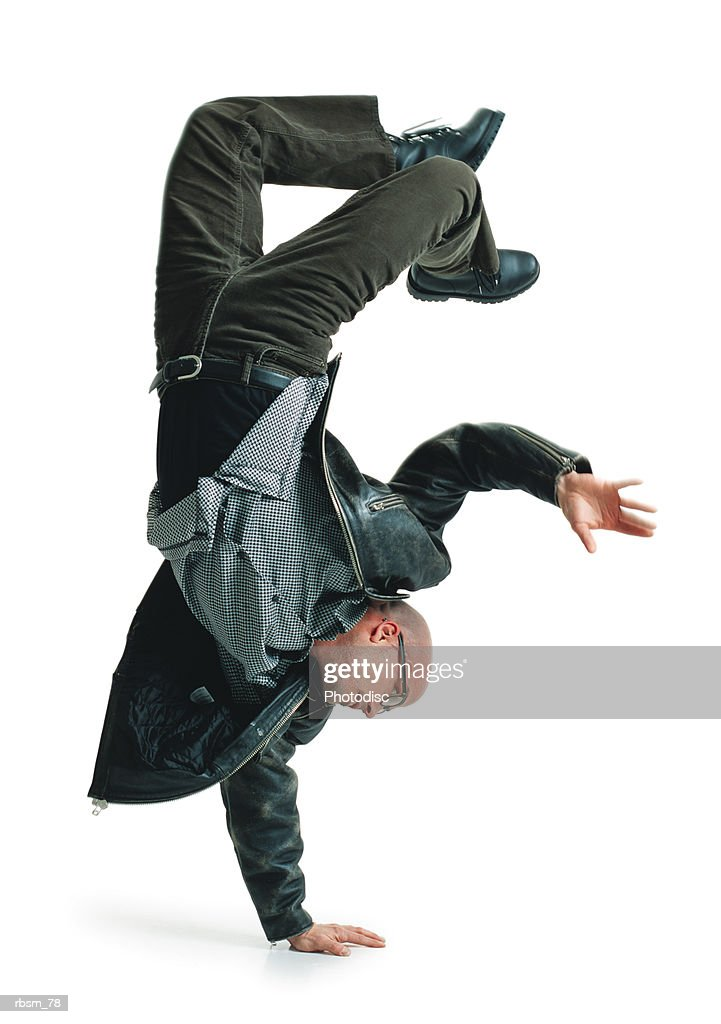 young bald male modern dancer in green pants and leather jacket balances upside down on one hand : Foto de stock