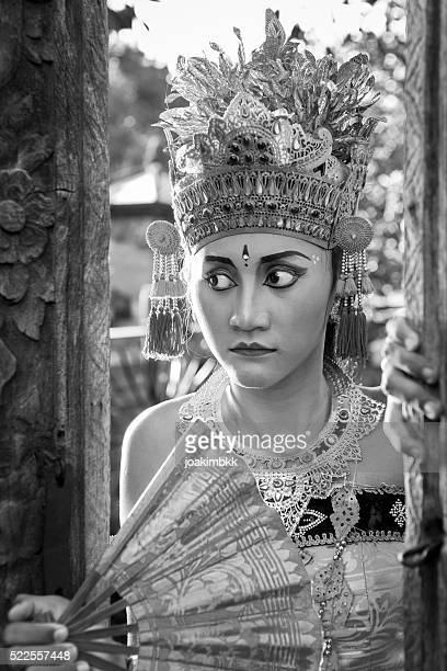 young bali dancer in traditional costume staring through a door - denpasar stock pictures, royalty-free photos & images