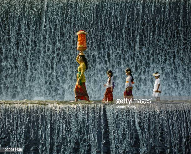 Young Balinese woman and children wearing traditional clothing, walking across waterfall