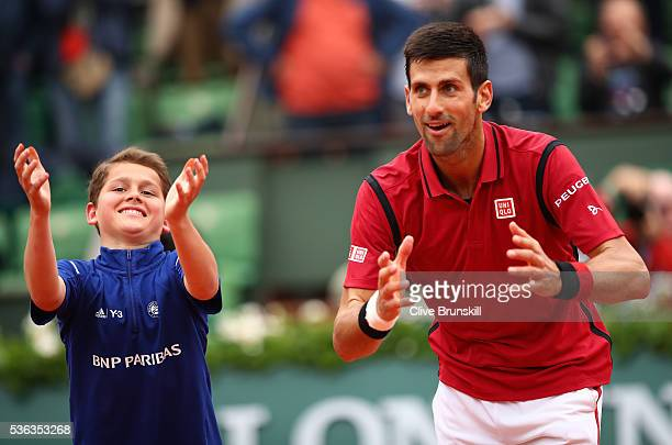 A young ball boy joins Novak Djokovic of Serbia as he celebrates victory during the Men's Singles fourth round match against Roberto Bautista Agut of...