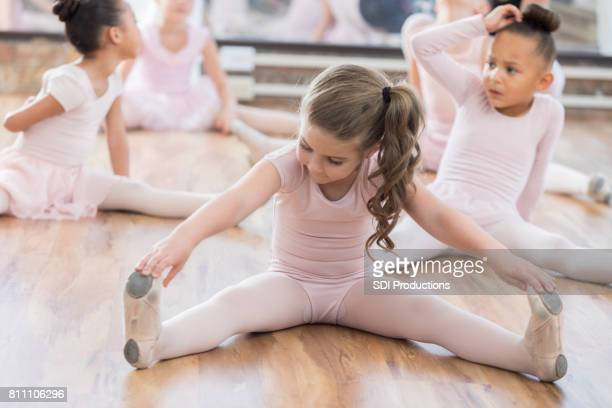 young ballerina and classmates stretch legs - little girls dressed up wearing pantyhose stock photos and pictures