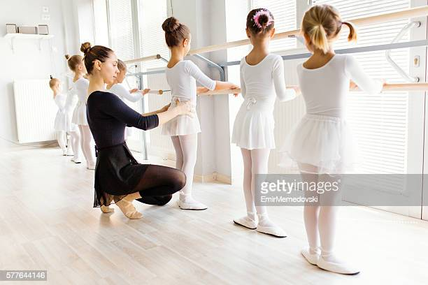 Young ballerina assisting little girls on a ballet class.