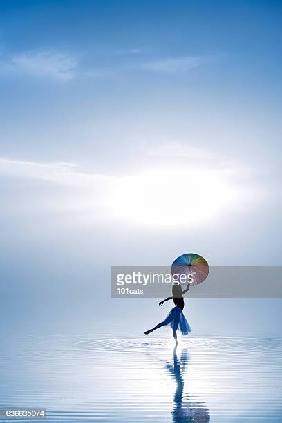 Young ballerina dancing with color umbrella on the salt lake
