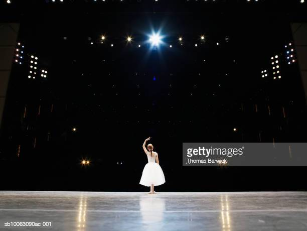 Young ballerina on stage, rear view