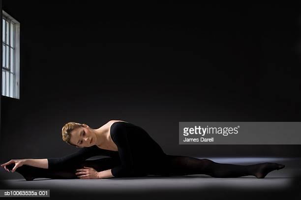Young ballerina performing splits in dark interior