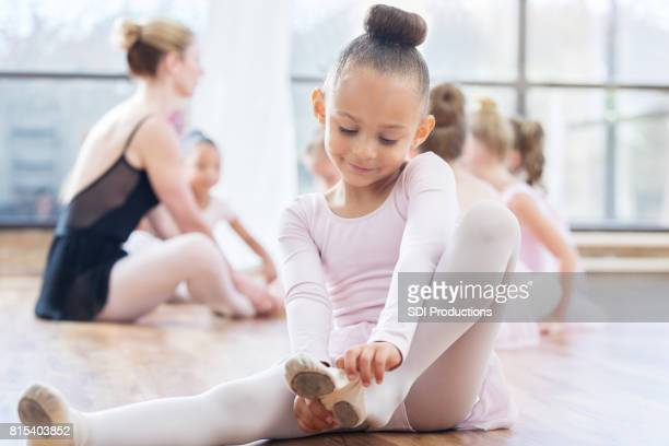 young ballerina sits and puts on ballet shoes before class - little girls dressed up wearing pantyhose stock photos and pictures