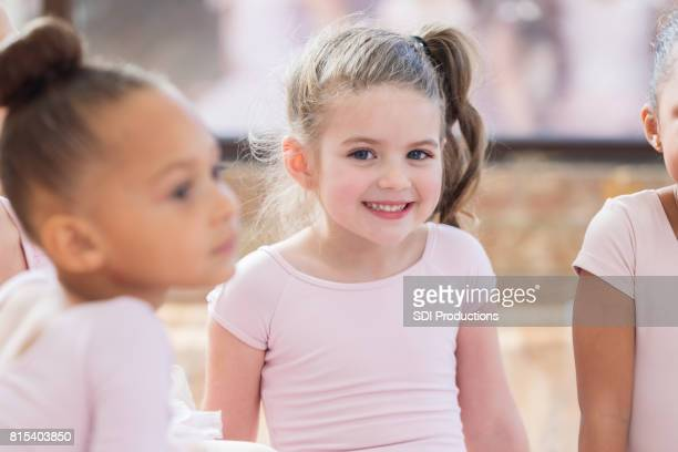 Young ballerina sits with friends and smiles during a class break