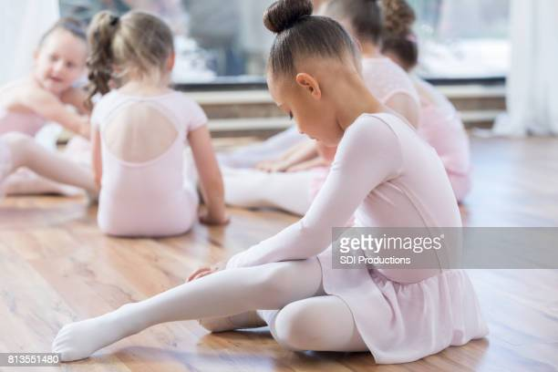 young ballerina stretches on floor before class - little girls dressed up wearing pantyhose stock photos and pictures