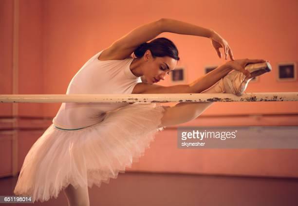 Jungen Ballerina erstreckt sich auf einer Barre im Tanzstudio.