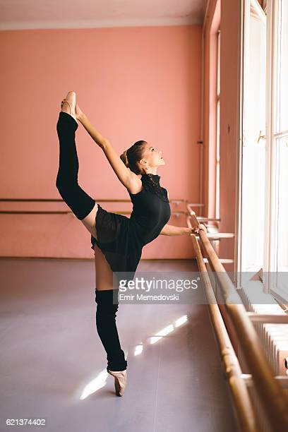 Young ballerina tip toeing next to a barre