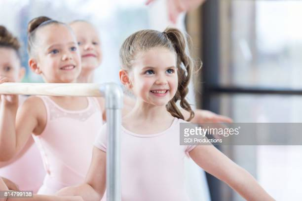 Young ballerina watches instructor during ballet barre exercises