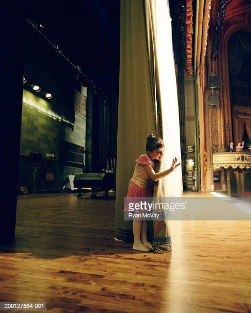 Young ballerina (6-8) waving behind theater curtain