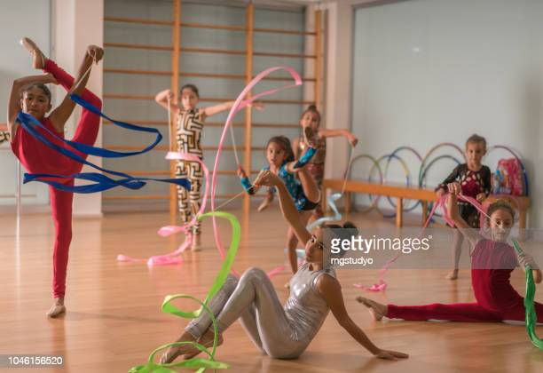 young ballerinas dancing doing practice in ballet studio. - rhythmic gymnastics stock pictures, royalty-free photos & images