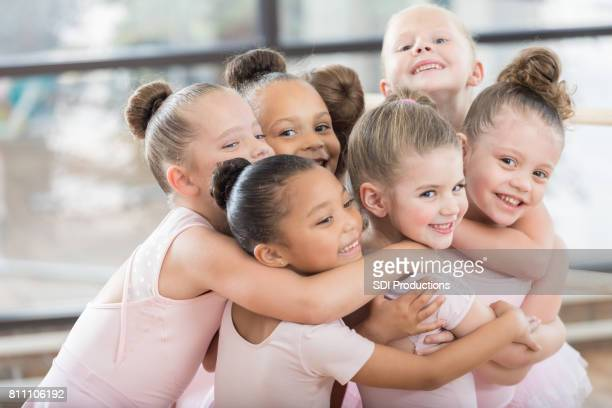 young ballerinas form a smiling group hug - ballet dancer stock pictures, royalty-free photos & images
