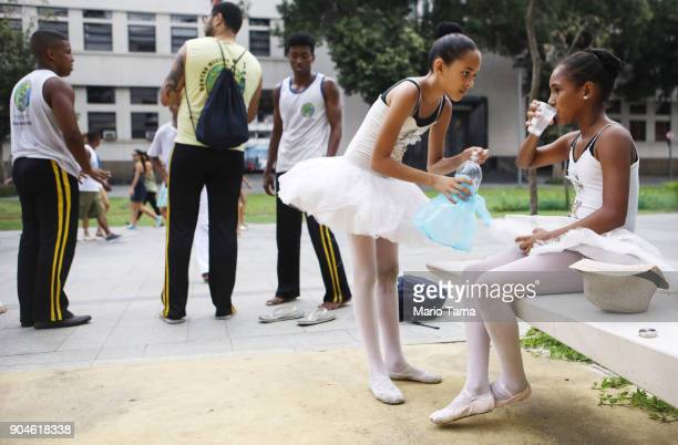 Young ballerinas from the project 'Dancando Para Nao Dancar' take a break after a street performance near Maua Plaza on January 13 2018 in Rio de...