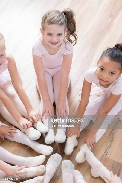 young ballerinas look up at camera as they sit in circle with feet together - little girls dressed up wearing pantyhose stock photos and pictures