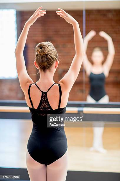 young ballet dancer posing in-front of mirror - little girls leotards stock photos and pictures