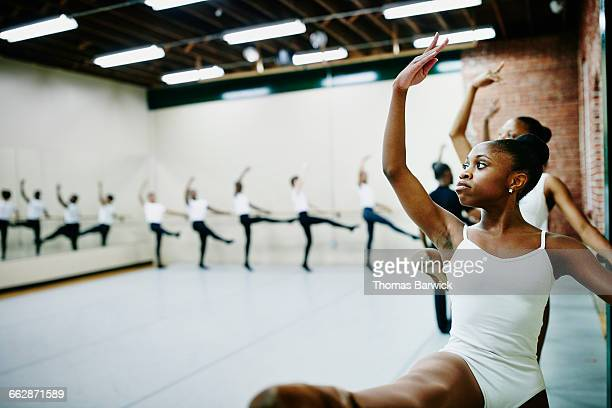 Young ballet dancers practicing at barre in studio