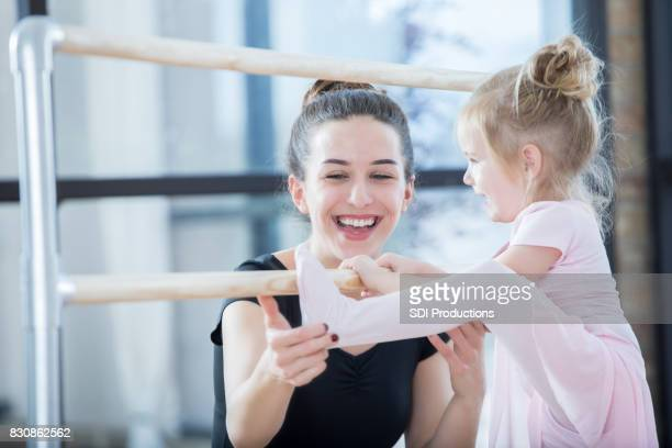 Young ballet instructor encourages preschool age student at ballet barre