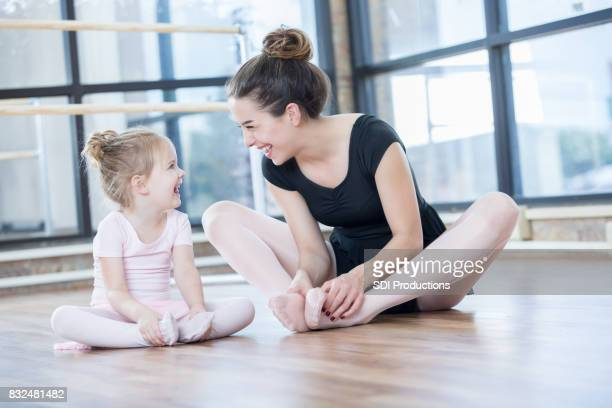 young ballet instructor laughs with preschool age student - little girls dressed up wearing pantyhose stock photos and pictures